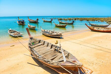 Rows of many traditional wooden fishing long tail boats moored at tropical sand beach with rocks