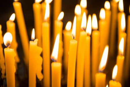 Many burning yellow wax candles in church. Venice, Italy