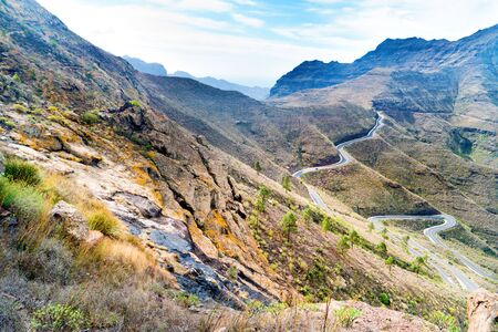 Nature landscape of Canary Island with mountain range, green hills and curvy road Stockfoto