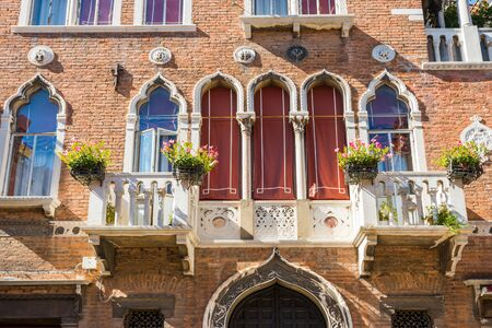 Facade of old building with typical Venetian windows and white balkony with flower pots. Venice, Italy