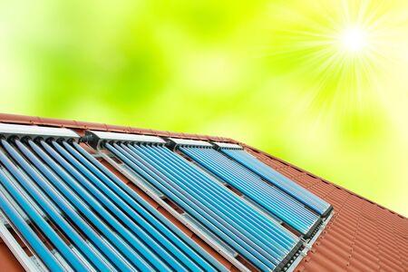 Vakuumkollektoren - Solarwarmwasserbereitungssystem auf rotem Dachhaus mit grünem Frühlingssonnenhintergrund