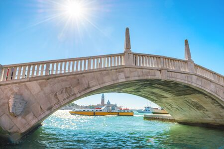 Beautiful view to white bridge over canal and exit to bay. Venice, Italy