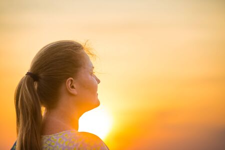 Silhouette of young woman looking to beautiful yellow sunset