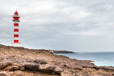 Striped red and white lighthouse at rocky coast of Gran Canaria island, Spain Stockfoto