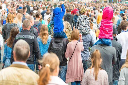 Tłum ludzi chodzących po ulicy miasta