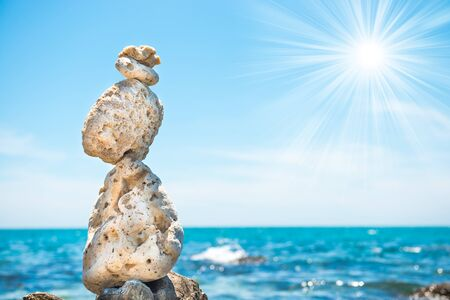 Zen stones balance at stony beach and sea background