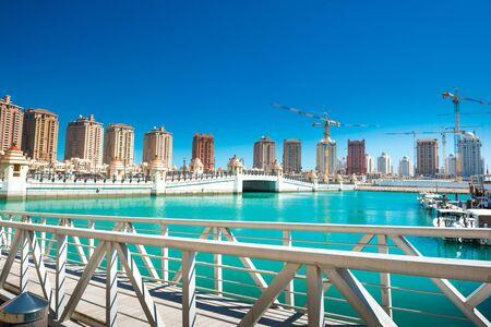 Luxury residential buildings of Pearl-Qatar and white yachts at Porto Arabia marina. Doha, Qatar
