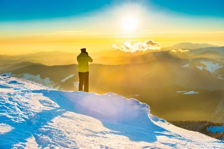 A man looking at sun and beautiful sunset in winter mountains with snow Фото со стока - 134853620
