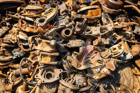 Closeup view of pile of old rusty metal scrap, used machine spares and car parts can be used as mechanic industrial background