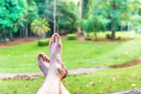Bare feet of resting man on green lawn background. Erawan National park, Thailand. Relax lifestyle concept