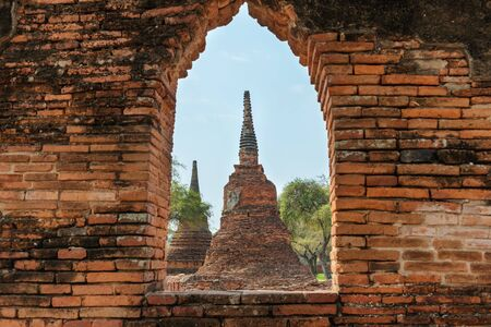 Historical architecture of Thailand - ruins of old Siam capital Ayutthaya. View to stupas of Wat Pra Si Sanphet temple from window in brick wall