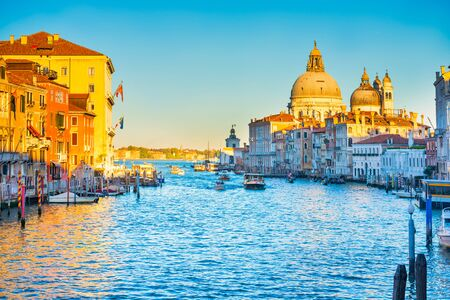 Sunset view of Grand Canal with boats and Basilica Santa Maria della Salute. Venice, Italy