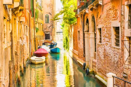 Morning in Venice street with canal, boats and gondolas