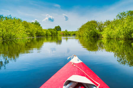 Kayak trip on blue river landscape and green forest with trees blue water clouds sky