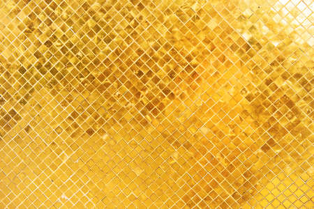 Closeup view of wall surface with many gold shiny mosaic squares. Can be used as metallic background