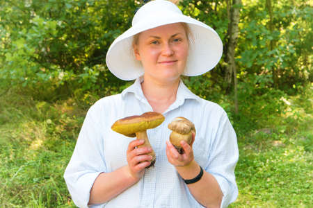 Pretty young woman in forest with big Boletus Edulis or Penny Bun mushrooms in hands 版權商用圖片