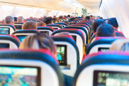 People flying sitting in plane interior with multimedia screens 版權商用圖片