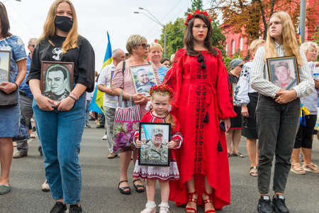 KIEV, UKRAINE - AUGUST 24, 2020: Girl with portrait of her killed in war farther on March of defenders, parade in Kyiv, dedicated to the Independence Day of Ukraine, 29th anniversary. 版權商用圖片 - 155239881