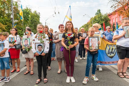KIEV, UKRAINE - AUGUST 24, 2020: People with portraits of their killed in war relatives on March of defenders, parade in Kyiv, dedicated to the Independence Day of Ukraine, 29th anniversary. 版權商用圖片 - 155239879