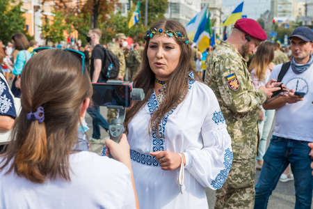 KIEV, UKRAINE - AUGUST 24, 2020: Sophia Fedyna in national Ukrainian clothes vyshivanka gives interview on March of defenders, parade in Kyiv, dedicated to the Independence Day of Ukraine, 29th anniversary. 版權商用圖片 - 155239886