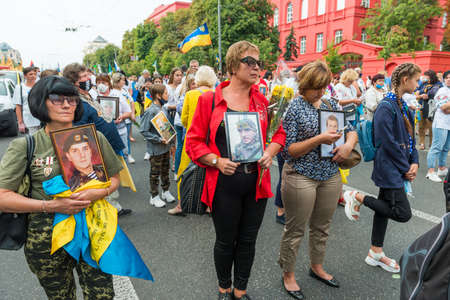 KIEV, UKRAINE - AUGUST 24, 2020: People with portraits of their killed in war relatives on March of defenders, parade in Kyiv, dedicated to the Independence Day of Ukraine, 29th anniversary. 版權商用圖片 - 155239888