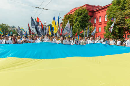 KIEV, UKRAINE - AUGUST 24, 2020: People with Ukrainian flag on March of defenders, parade in Kyiv, dedicated to the Independence Day of Ukraine, 29th anniversary. 版權商用圖片 - 155239854