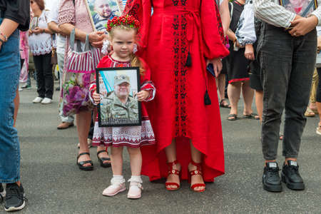 KIEV, UKRAINE - AUGUST 24, 2020: Girl with portrait of her killed in war farther on March of defenders, parade in Kyiv, dedicated to the Independence Day of Ukraine, 29th anniversary. 에디토리얼