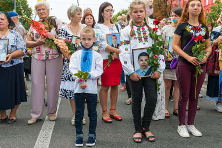 KIEV, UKRAINE - AUGUST 24, 2020: Children with portraits of their killed in war farthers on March of defenders, parade in Kyiv, dedicated to the Independence Day of Ukraine, 29th anniversary.