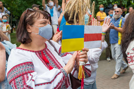 KIEV, UKRAINE - AUGUST 24, 2020: Woman with Ukrainian and Belarus flags on March of defenders, parade in Kyiv, dedicated to the Independence Day of Ukraine, 29th anniversary. 에디토리얼