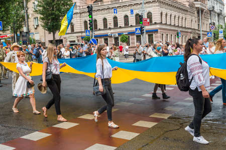 KIEV, UKRAINE - AUGUST 24, 2020: People, young women with Ukrainian flag on March of defenders, parade in Kyiv, dedicated to the Independence Day of Ukraine, 29th anniversary.