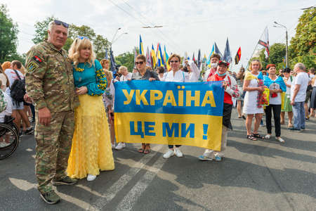"""KIEV, UKRAINE - AUGUST 24, 2020: People with """"Ukraine is Us"""" banner on march of defenders, parade in Kyiv, dedicated to the Independence Day of Ukraine, 29th anniversary."""