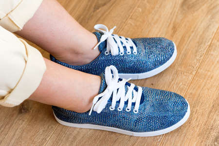 Casual blue shoes sneakers on women's feet on wooden floor background