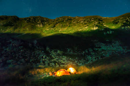 Two orange glowing illuminated tents at night in mountains with night stars 版權商用圖片