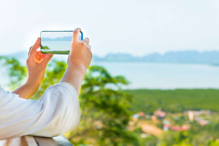 Young woman with mobile phone taking image of Thailand mountain island sea landscape Reklamní fotografie