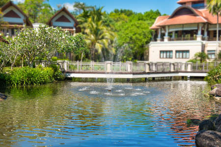View of beautiful green pond with fountain and buildings of luxury hotel at tropical resort