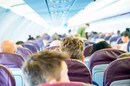 Passengers sit inside airplane - people traveling