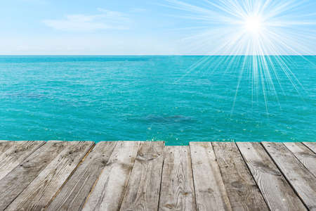 Blue sea with sun, water summer background, view from wooden table