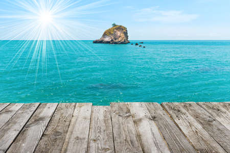 Rock island in blue sea, view from wooden table