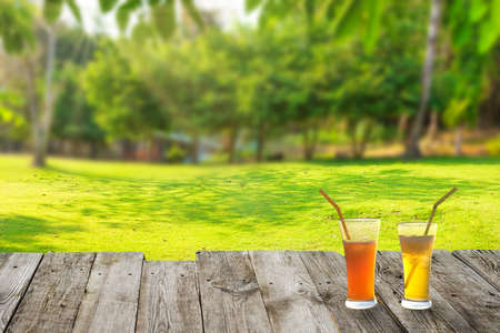Green grass field lawn with 2 cocktail glasses on wooden table. Spring summer holiday landscape Reklamní fotografie
