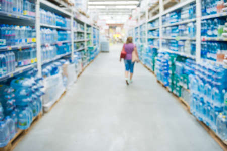 Market shop and supermarket interior with drink water section as blurred store background