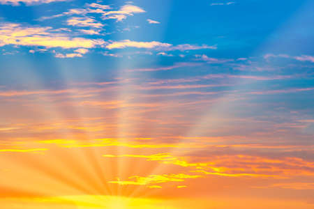 Sunset sky with sun rays and sunset clouds