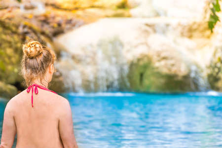 Rear view of red haired young woman in pink bikini swimsuit sitting at emerald blue tropical lake with waterfall. Erawan National park, Kanchanaburi, Thailand