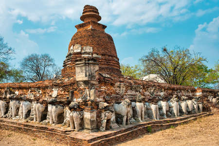 Row of elephant sculptures at ruins of brick chedi in Wat Maheyong temple. Historic architecture of Ayutthaya, Thailand