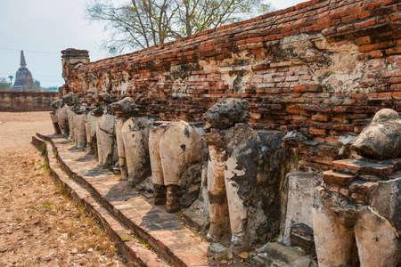 Row of elephant sculptures at ruins of brick Wat Maheyong temple. Historic architecture of Ayutthaya, Thailand