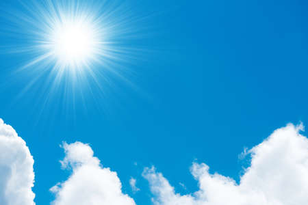 Beautiful fluffy white clouds on bright blue sky and shining sun with sun rays Banque d'images