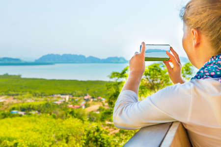 Young woman with mobile phone taking image of Thailand mountain island sea landscape Banque d'images