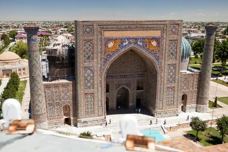 registan: View of SherDor Madrasa from Ulugbek Madrasa Registan Square Samarkand Uzbekistan. Stock Photo
