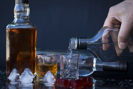 alcoholic drink: Pour vodka into a glass with ice, vodka and whiskey in glass with ice, alcoholic drink Stock Photo