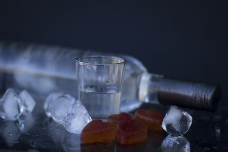 alcoholic drink: A bottle of vodka and a glass with ice, alcoholic drink, close-up on a black background