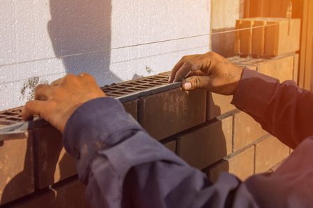 unravel: Bricklayer lays bricks under unravel. construction work